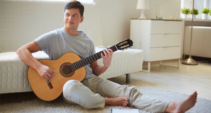 Nashvillian guy enjoying his clean carpet by sitting on it & playing guitar